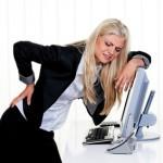 Frau mit Schmerzen im Rücken im Büro