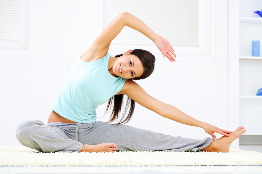 Smiling young woman doing stretching exercise.